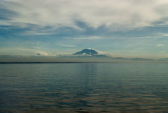 Volcano Mount Batur from the side of the lagoon: in the foreground there is a surface of water with reflections, in the distance a Royalty Free Stock Photography