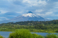 Volcano near the lake in cloudy weather Stock Images