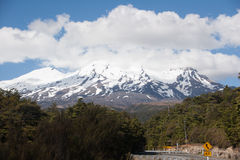 Volcano Ruapechu in New Zealand. Snow covered hills of volcano Ruapechu in a cloudy sky with forest and road in the foreground. Summer time, 2016. Ohakune. New Stock Images