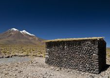 Volcano and a stone hut Stock Images