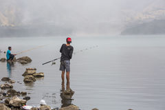 Volcano tourism. Locals from Indonesia are fishing in a volcanic lake Stock Photo