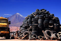 Volcano of Tyres. Old fuel Tanker, mountain of tyres and The Licancabur volcano lurking in background Royalty Free Stock Image