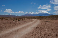 Volcanoes on the Altiplano. Snow and ice covered peaks of the volcanoes Parinacota (6342m) and Pomerape (6240m), tower above the altiplano in Lauca National Park Royalty Free Stock Photos