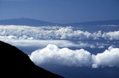 Volcanoes and clouds. A view of the Mauna Loa and Mauna Kea Volcanoes surrounded by blue sky and fluffy white clouds.  Taken in Haleakala National Park in Maui Stock Photography