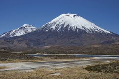 Volcanoes in Lauca National Park. Volcanoes Parinacota and Pomerape in Lauca National Park high on the Altiplano of northern Chile. In the foreground lakes known Royalty Free Stock Photo