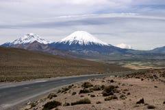 Volcanoes and Parinacota Pomerape. Pomerape and Parinacota volcanoes in the Chilean Altiplano Stock Photos
