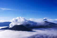 Volcanoes seen at a distance from Mount Penanjakan Indonesia. White smoke coming out of volcanoes surrounded by white clouds of mist and a clear blue sky seen Stock Images