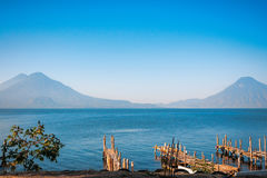 Volcanoesview at lake Atitlan. Old rickety wooden piers out into Lake Atitlan in Guatemala on the shore in Panajachel with volcanoes in the background: on the Royalty Free Stock Photos