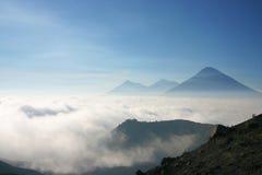 Volcans au-dessus d'un voir des nuages Photographie stock libre de droits