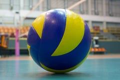 voleibol Amarelo-azul no assoalho no gym fotografia de stock royalty free