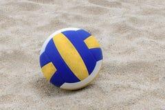 Voleibol azul e amarelo na praia e pegada nas areias imagens de stock