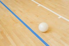 Voleibol blanco en el piso en el gimnasio imagen de archivo
