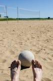 Voleibol de playa con el cielo azul y red y pies Foto de archivo libre de regalías
