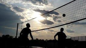 Voleibol de playa profesional en la puesta del sol en la cámara lenta