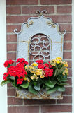 Volendam. Planter. Metal planter with flowers on a brick wall Royalty Free Stock Photography