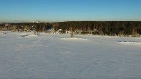 Voler au-dessus de la mer congelée Forêt sur les banques Voler le long du rivage banque de vidéos