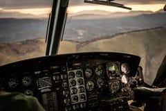 Voler dans le coucher du soleil au-dessus des montagnes dans l'habitacle Images libres de droits