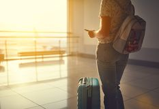 Voler de attente de jeune femme à l'aéroport à la fenêtre avec des suitcas Photo libre de droits