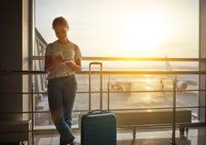 Voler de attente de jeune femme à l'aéroport à la fenêtre avec des suitcas Photos libres de droits