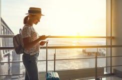Voler de attente de jeune femme à l'aéroport à la fenêtre avec des suitcas Images libres de droits