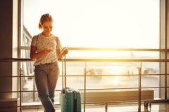 Voler de attente de jeune femme à l'aéroport à la fenêtre avec des suitcas Photos stock