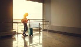 Voler de attente de jeune femme à l'aéroport à la fenêtre avec des suitcas Images stock