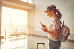 Voler de attente de jeune femme à l'aéroport à la fenêtre avec des suitcas Photographie stock