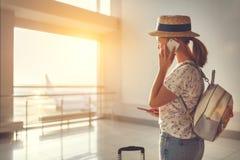 Voler de attente de jeune femme à l'aéroport à la fenêtre avec des suitcas Image stock