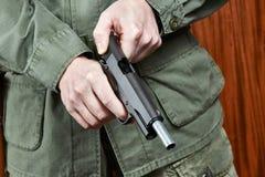 Volet de soldat entassant l'arme à feu de pistolet Images stock