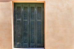 Volet en bois des abat-jour à une fenêtre et à un mur plâtré Images stock