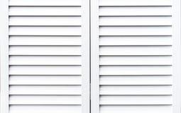 Volets en bois blancs pour protéger des fenêtres contre la lumière du soleil image libre de droits