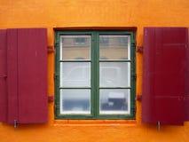 Volets rouges colorés sur une fenêtre. Images stock