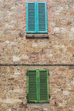 Volets verts et bleus sur le mur en pierre Images stock