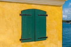 Volets verts sur le mur jaune de stuc Photos libres de droits