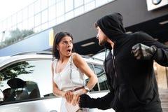 Voleur agressif de jeune homme dans le hoodie volant la femme effrayée photographie stock libre de droits