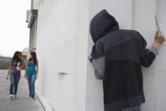 Voleur avec le couteau se cachant derrière faisant le coin et attendant deux filles Images libres de droits