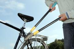 Voleur braeking outre d'un blocage de bicyclette avec un outil Images stock