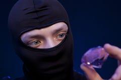 voleur Homme dans le masque noir avec une grande émeraude Photos libres de droits