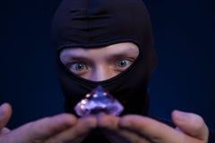 voleur Homme dans le masque noir avec une grande émeraude Photographie stock libre de droits