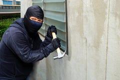 Voleur masqué à l'aide d'un marteau essayant de casser des fenêtres photos stock