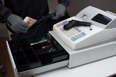 Voleur prenant l'argent à partir de la caisse enregistreuse photos stock