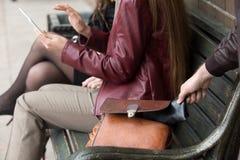 Voleur volant le portefeuille de la femme s'asseyant sur un banc image libre de droits