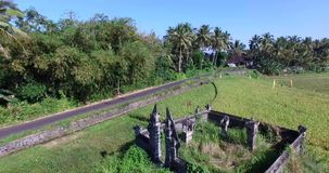 Volez à travers un petit temple au milieu des gisements de riz dans Bali banque de vidéos