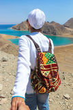 Volg me aan het overzees, een vrouw met een kleurrijke backbagrubriek aan het overzees met bergen Stock Foto's