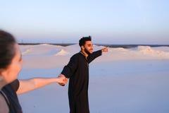 Volg me Arabische kerel en de Europese vrouw die langs loopt dient deser in Stock Foto