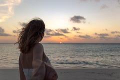 Volg me concept jonge vrouw die op een strand zonsondergang bekijken stock afbeelding