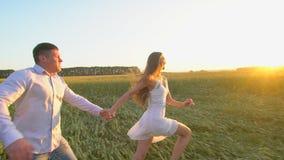 Volg me De gelukkige handen van de paarholding, in openlucht lopend op gouden tarwegebied en hebbend pret, Paar die op weide lope stock footage