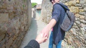 Volg me Een jonge kerel in een GLB leidt een meisje door de hand langs de oude straten van Carcassonne in Frankrijk stock video