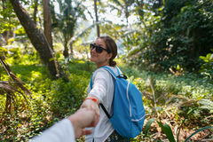 Volg me reis concept Achtermening van jonge vrouw met rugzak die in openlucht de vriend` s hand ontdekken van de wildernisholding Royalty-vrije Stock Fotografie