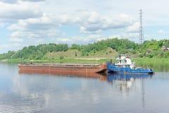 Volga, Rússia - 2 de junho 2016 Um reboque do rio empurra uma barca ao longo do rio de Volka perto de um banco verde coberto com  Fotos de Stock Royalty Free